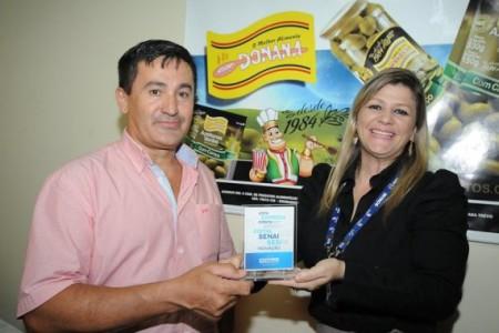 Daniely Sotolani, do Instituto Senai, entrega troféu ao proprietário da Donana Alimentos, Antônio Lucena